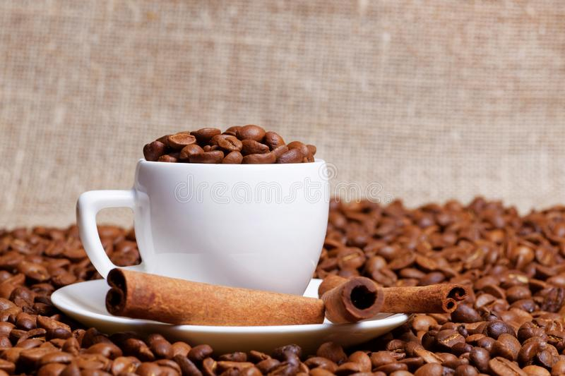 Coffee cup demitasse full of coffee beans and cinnamon sticks in the heap coffee beans stock images