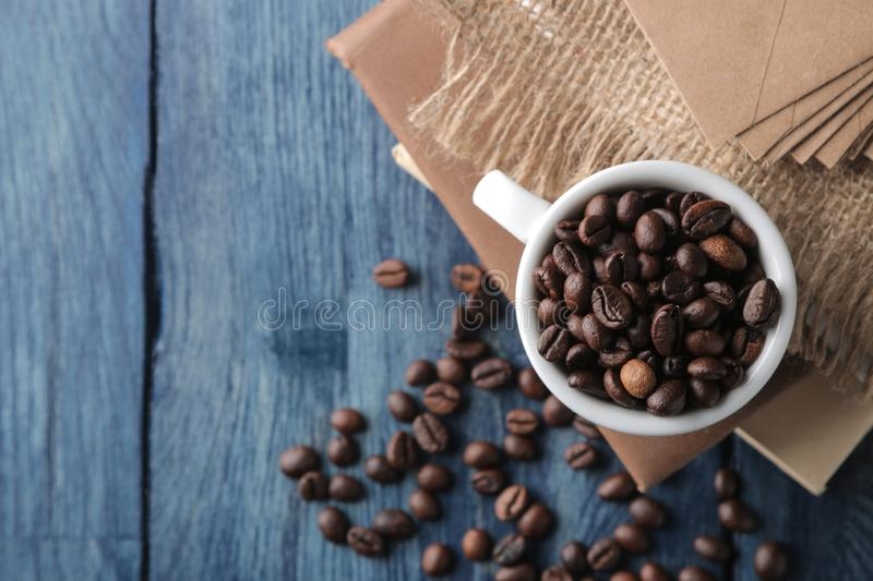Coffee cup for espresso and coffee beans on a blue wooden table with place for text. Top view royalty free stock photos