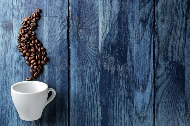 Coffee cup for espresso and coffee beans in the form of smoke on a blue wooden table with space for an inscription royalty free stock photo