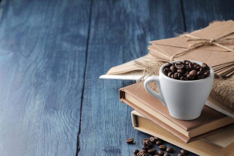 Coffee cup for espresso and coffee beans on a blue wooden table with space for inscription royalty free stock photography