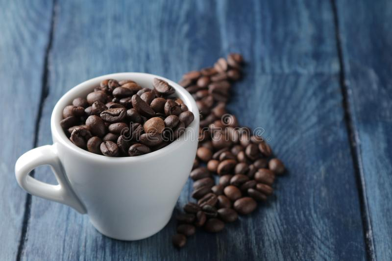 Coffee cup for espresso and coffee beans on a blue wooden table with space for inscription stock images