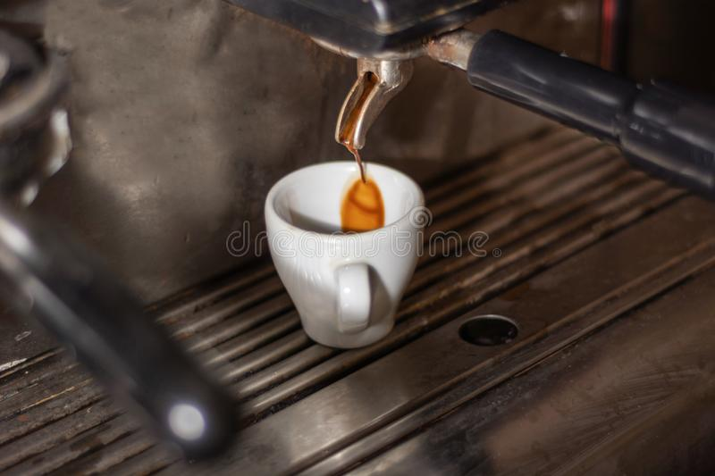 Coffee cup on an espresso machine and coffee drip in a cup. Process of making espresso coffee on the old machine in a pub kitchen. Close up, selective focus royalty free stock image