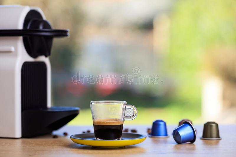 Coffee cup and espresso maker and capsules on blur background, Closeup view with details. Coffee cup and espresso machine and capsules on wooden table, blur royalty free stock photo