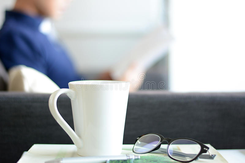 Coffee cup, eye glasses & pen over a book with blur background of a man stock photo