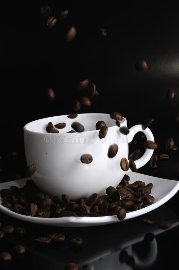 Coffee cup with failing coffee beans royalty free stock image