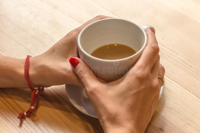 Coffee cup in female hands. White cup of coffee in female hands. Warm your hands with a cup of hot drink. Meeting in a cafe. The girl in the coffee shop. Morning royalty free stock photography