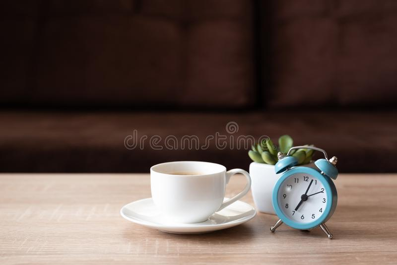 Coffee cup, flower pot and clock on wooden table against defocused sofa with pillows. Front view. Good morning concept. Mock-up.  royalty free stock photos
