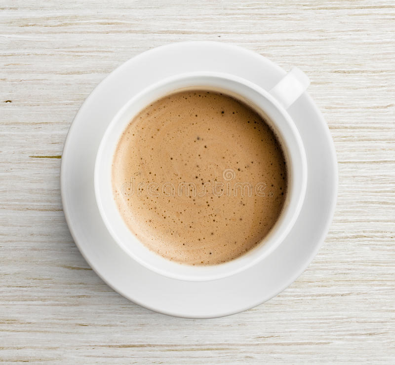 Coffee cup with foam on wooden table top view royalty free stock photo