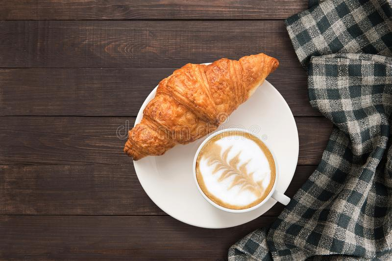 Coffee cup and fresh baked croissants near hand towel on wooden background. Top view, Copy space. royalty free stock photography