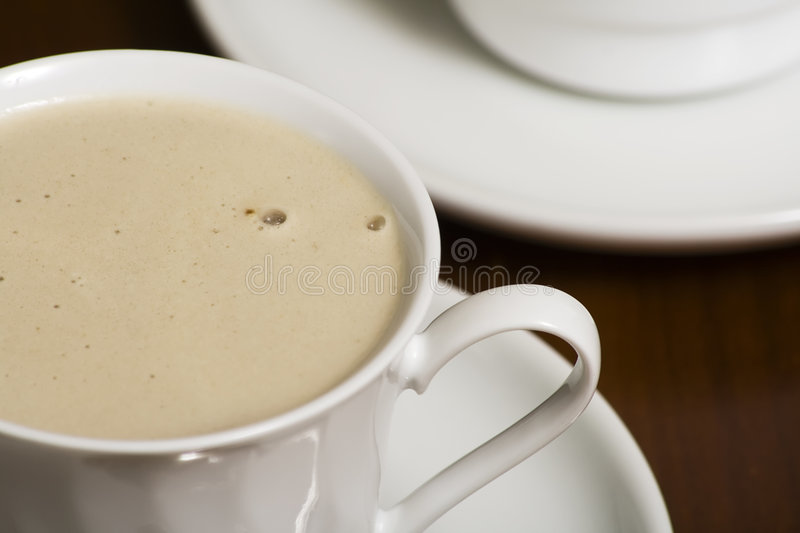 Coffee Cup with Froth. Close up of a coffee cup with froth and shallow DOF stock photography