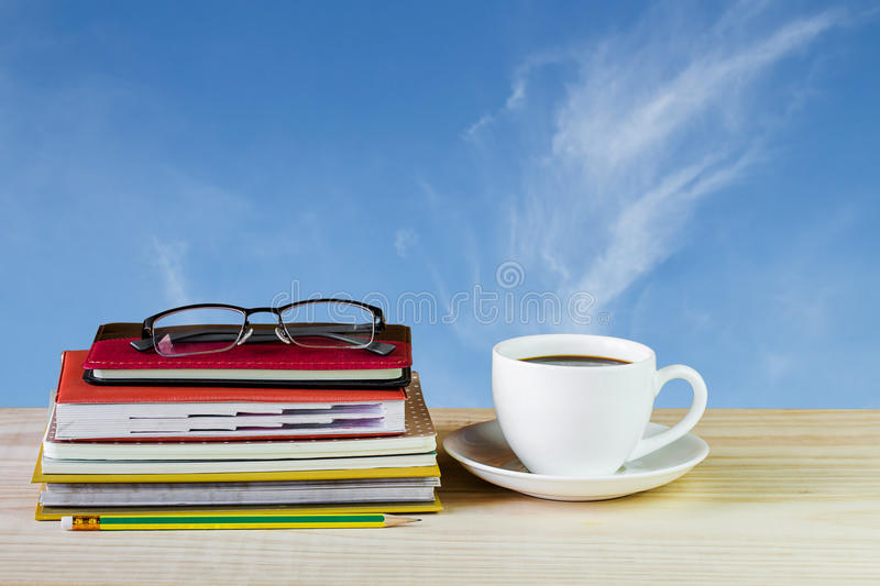 Coffee cup, glasses, and stack of book on wooden table with blur royalty free stock photo