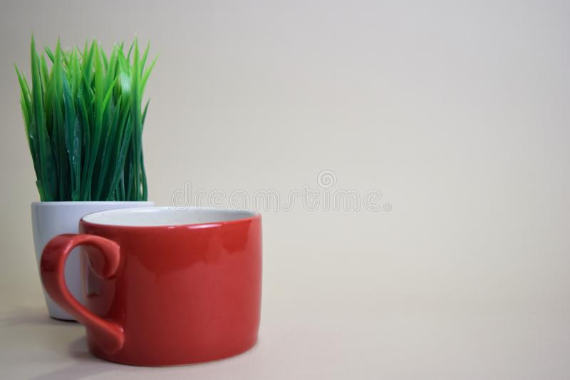 Coffee cup and grass pot isolated on brown background royalty free stock photos