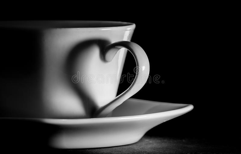 Coffee cup; the handle of the cup silhouettes a heart royalty free stock image