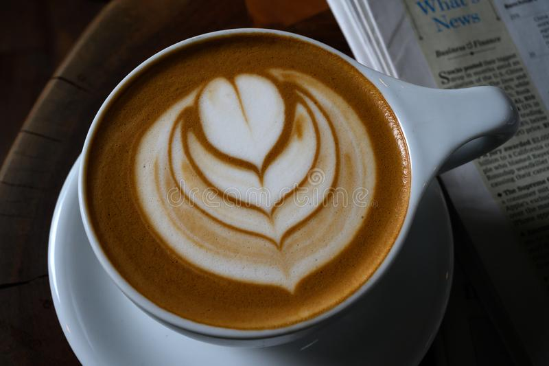 Coffee cup with heart in foam. White coffee cup with a cafe mocha and heart in foam newspaper in background royalty free stock image
