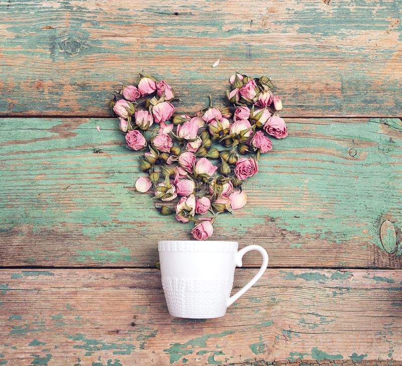 Coffee cup with heart from pink rose flowers coming out of it on old turquoise wooden background. royalty free stock photo