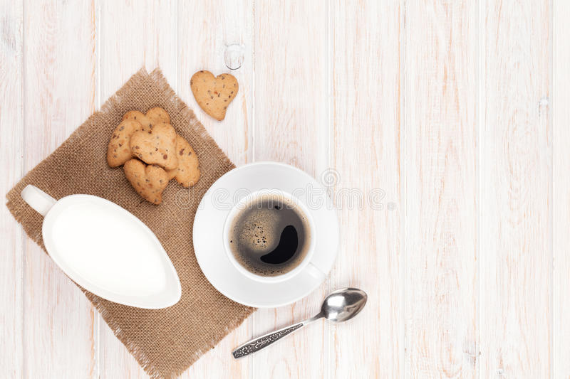Coffee cup, heart shaped gingerbread cookies and milk pitcher. On white wooden table with copy space stock photo