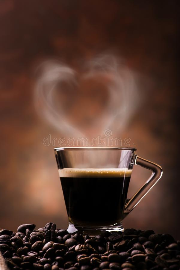 Coffee in a cup with heart-shaped steam. From the cup of hot coffee the steam forms a heart stock photo