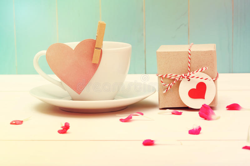 Coffee cup with heart tag and a small giftbox stock image