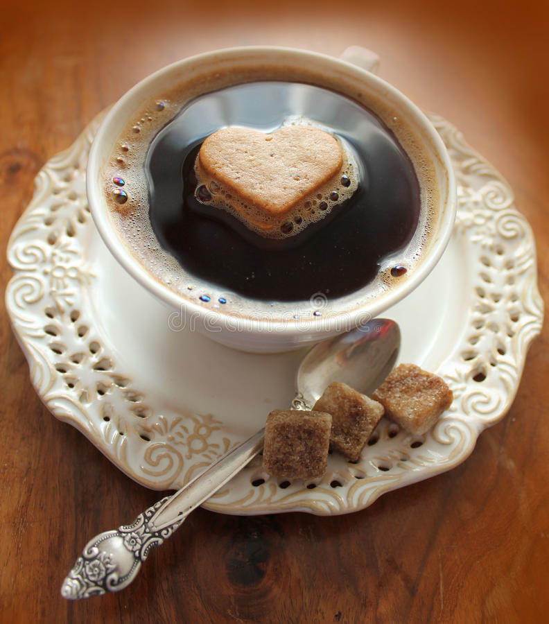 Coffee cup with heart on a wooden table stock image