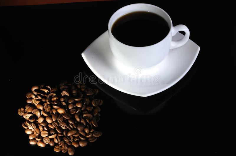 Coffee cup with highlited coffee beans royalty free stock image