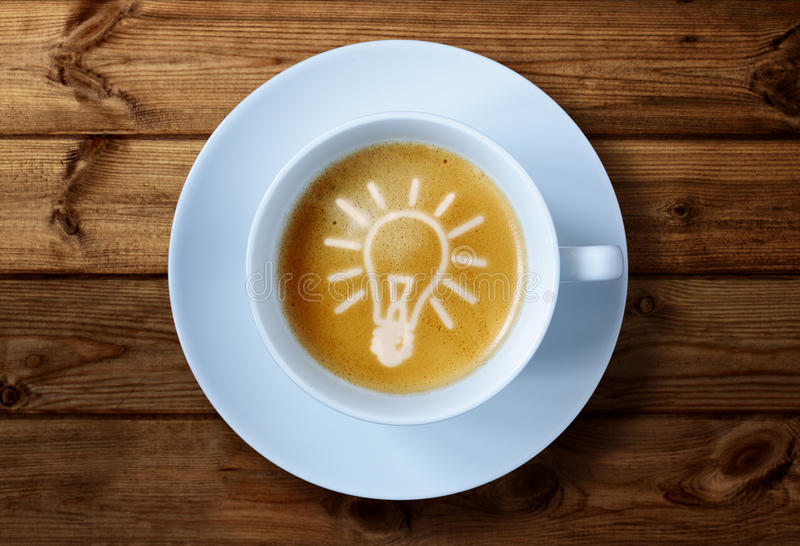 Coffee cup ideas. Coffee cup with light bulb idea in the froth concept for ideas, creativity and innovation royalty free stock photos
