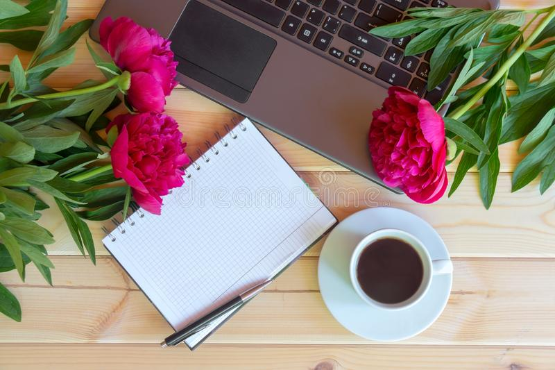 Coffee cup, laptop keyboard, empty notebook and red peony flowers. On wooden table. Top view, copy space stock images