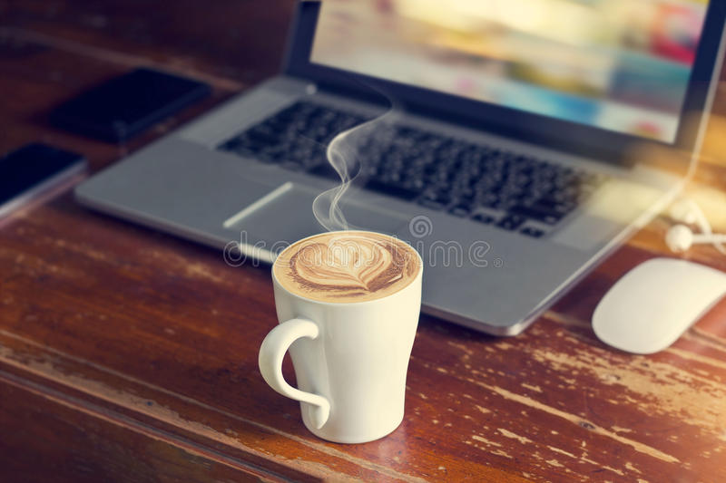 Coffee cup with laptop, mouse and earphone on old wooden table royalty free stock photos