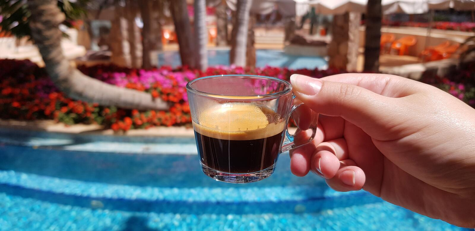 Coffee cup made from transparent glass in female hand against blue outdoor pool stock images
