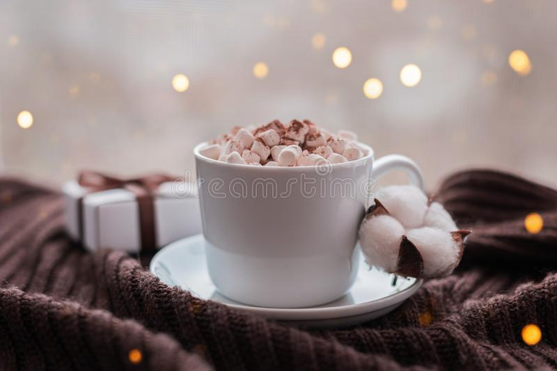 Coffee cup with marshmallow and gift box with brown ribbon on warm knitted brown blanket. Cozy and moody concept stock image