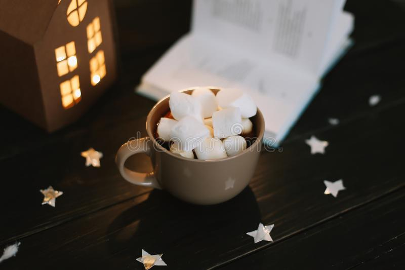 Coffee cup with marshmallows and a book on the table. Still life on dark background. royalty free stock photography