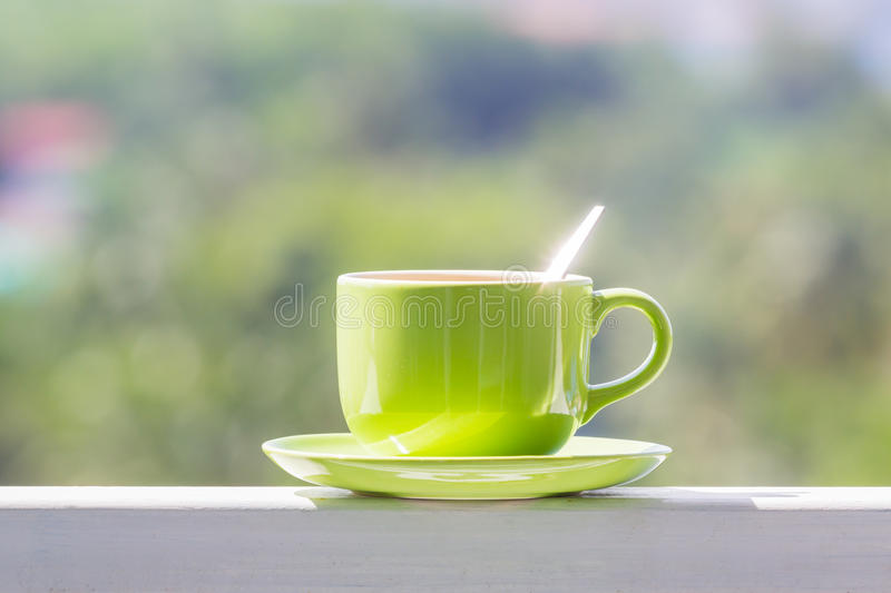 Coffee cup in the morning. Green coffee cup with spoon in the morning balcony stock photo