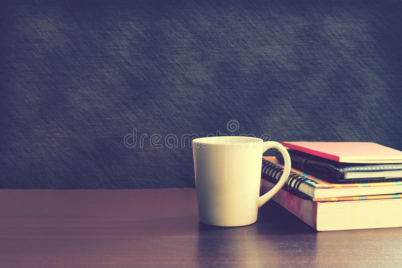 Coffee cup and notebook on wood table with backboard background. Coffee cup and notebook on wood table with backboard background stock photo