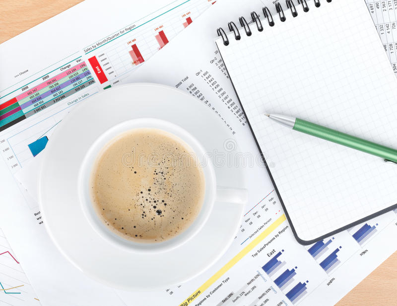 Coffee cup and notepad over papers with numbers and charts stock images