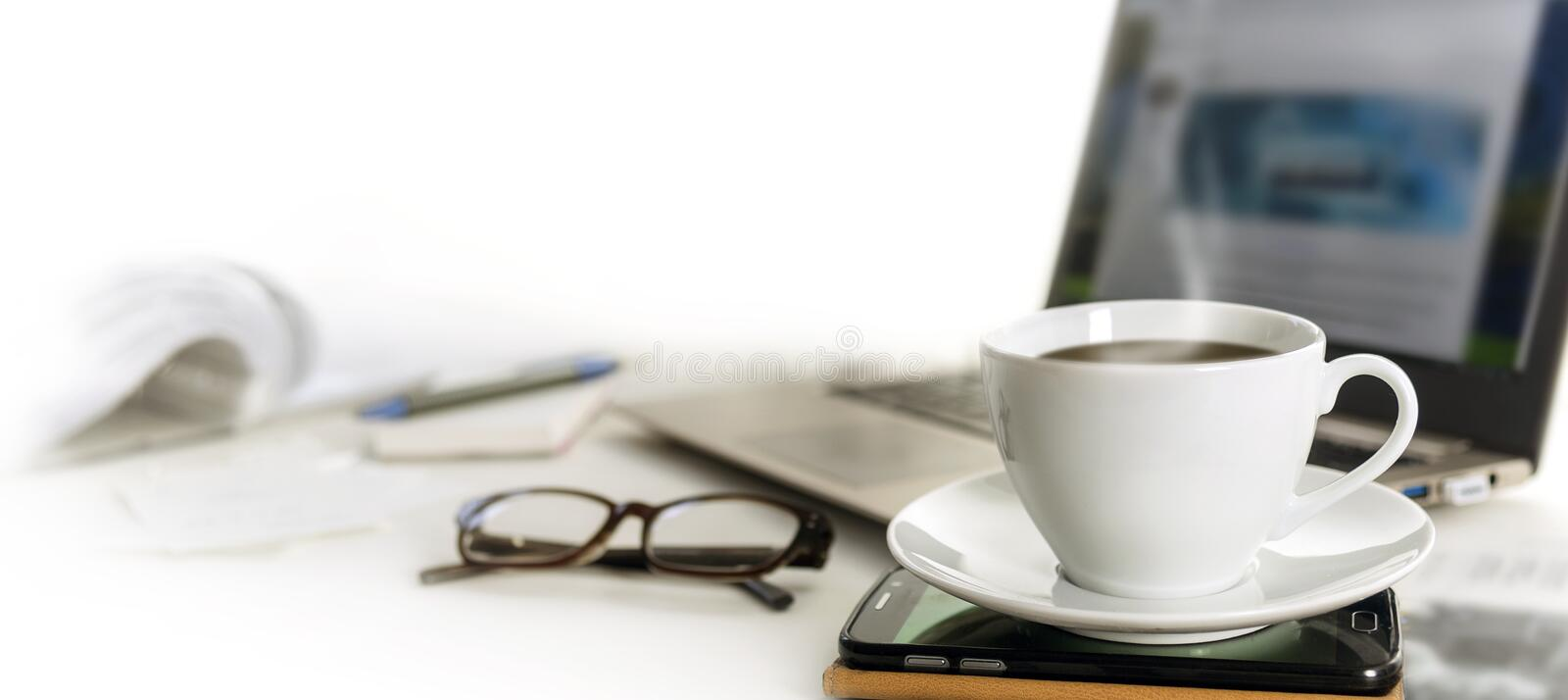 Coffee cup on an office desk with cell phone, laptop, glasses an. D papers, blurred background fades to white, panoramic banner format for web page header, copy royalty free stock photos