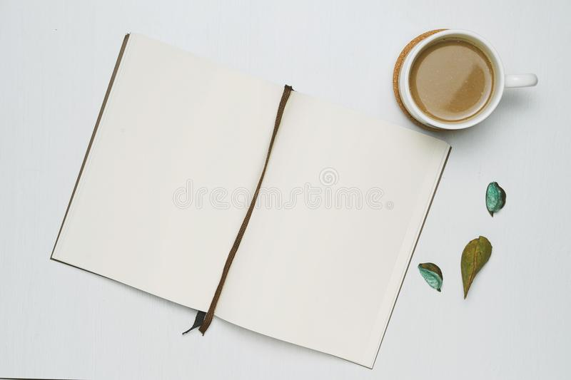 Coffee cup with open notebook on white wooden background. Minimal flat lay, Top view. royalty free stock photography