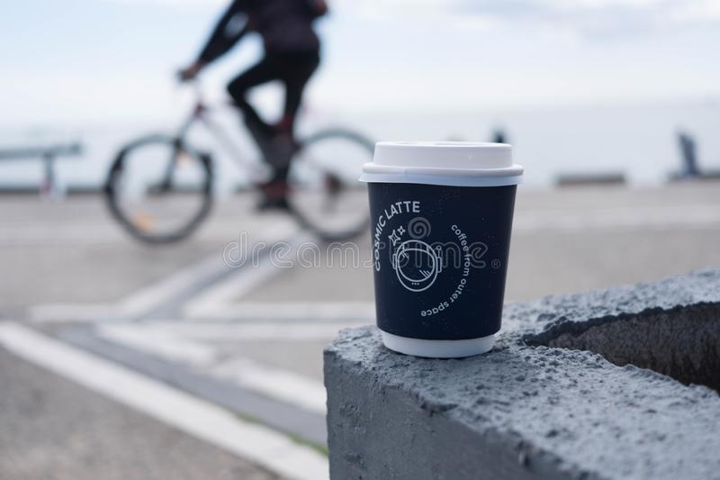 A coffee cup with a bicyclist in background. A coffee cup `Coffee from outer space` with a blurred bicyclist in background stock image