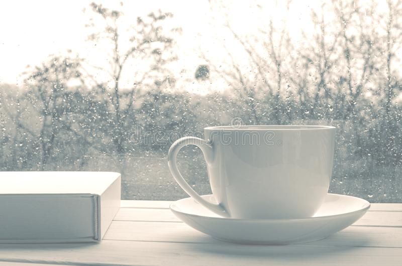 Coffee cup over mirror background in rainy day,copy space. Cozy home still life: Coffee cup over mirror background in rainy day,copy space, book, window, cold stock photo