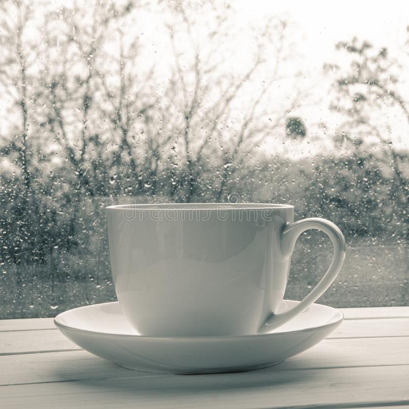 Coffee cup over mirror background in rainy day,copy space. Cozy home still life: Coffee cup over mirror background in rainy day,copy space, book, window, cold royalty free stock images