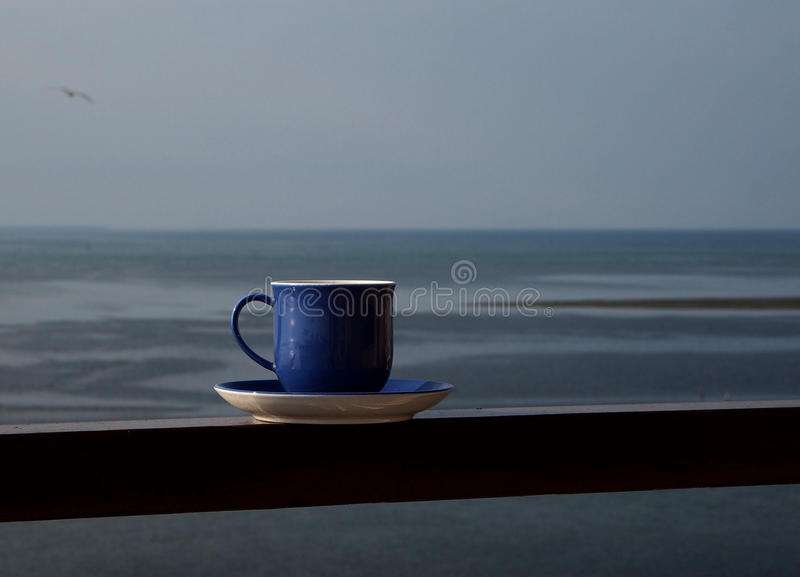 Coffee cup over the sea. Blue coffee cup over the sea stock photo