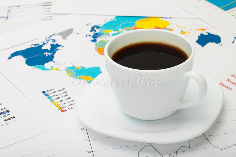 Coffee cup over world map and some financial documents. Studio shot royalty free stock images