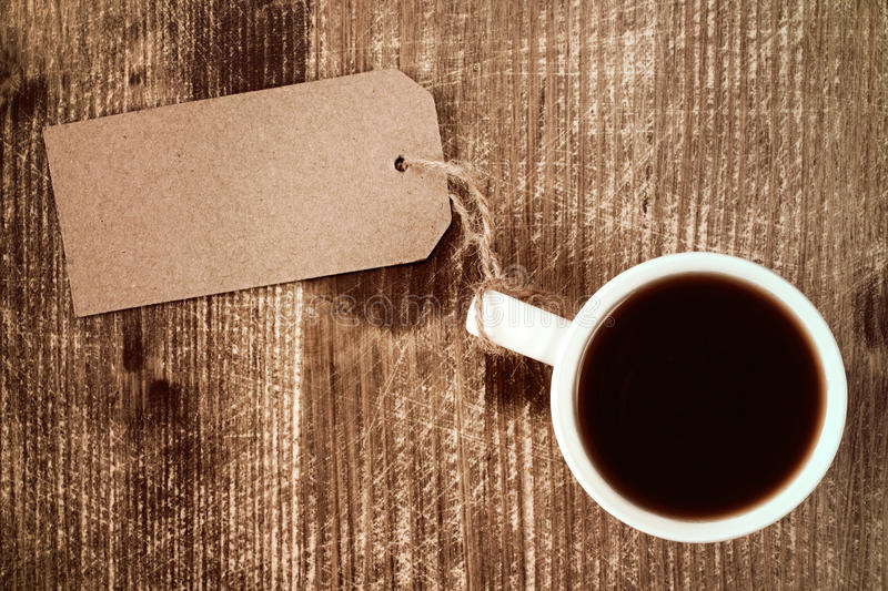 Coffee cup with paper blank tag. Coffee cup with paper blank tag on wooden background stock images