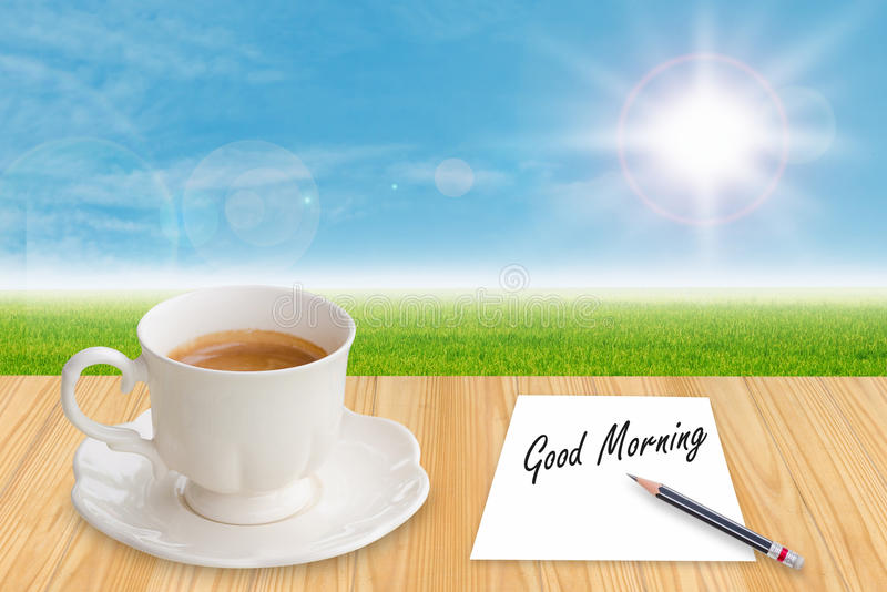 Coffee cup and paper with word Good morning. On table in morning royalty free stock image