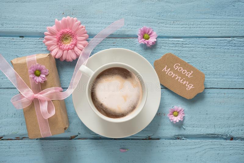 Coffee cup, pink flowers and a gift on pastel blue wood background with copy space, text Good Morning, top view from above royalty free stock photo