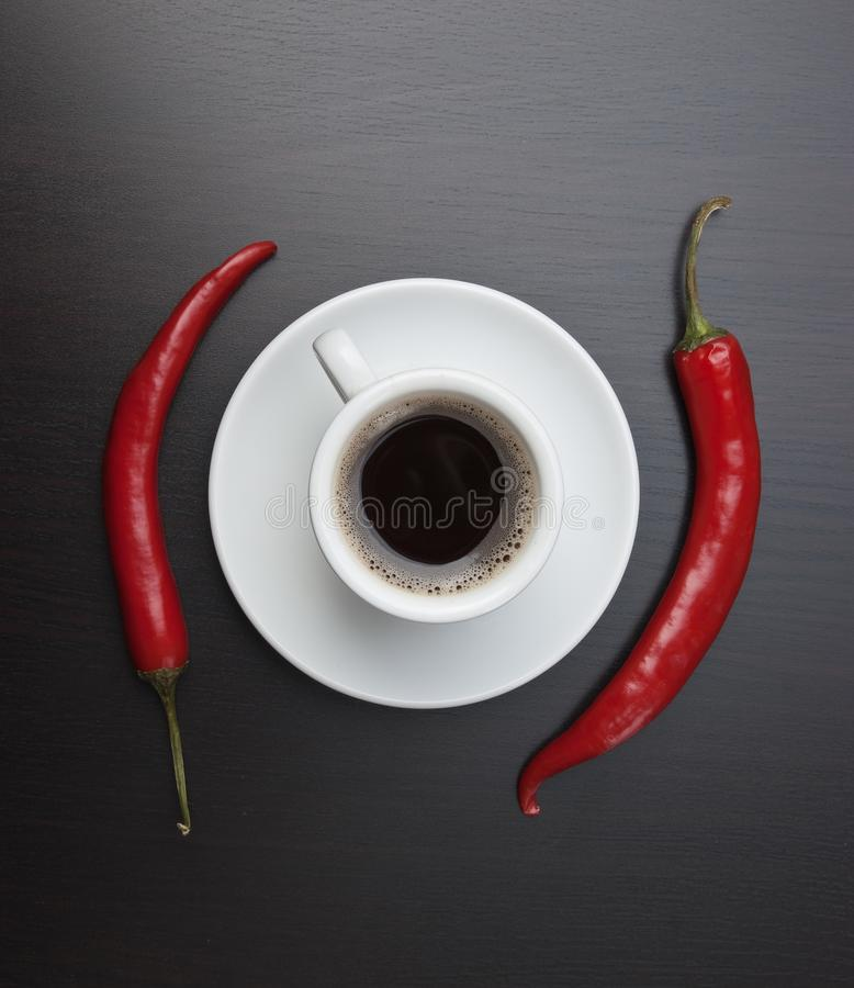 Coffee cup and red peppers. Coffee cup and red chili peppers royalty free stock image