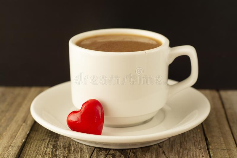 Coffee cup and red Heart on wooden background. Valentine's Day breakfast stock image