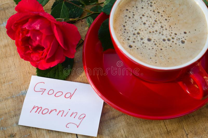 Coffee cup with red rose and notes good morning. Coffee cup with red rose flower and notes good morning on wooden rustic table from above, breakfast on Mothers royalty free stock image