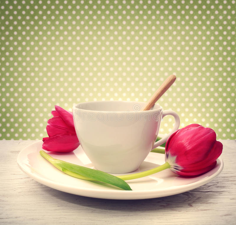 Coffee cup with red tulips royalty free stock photo