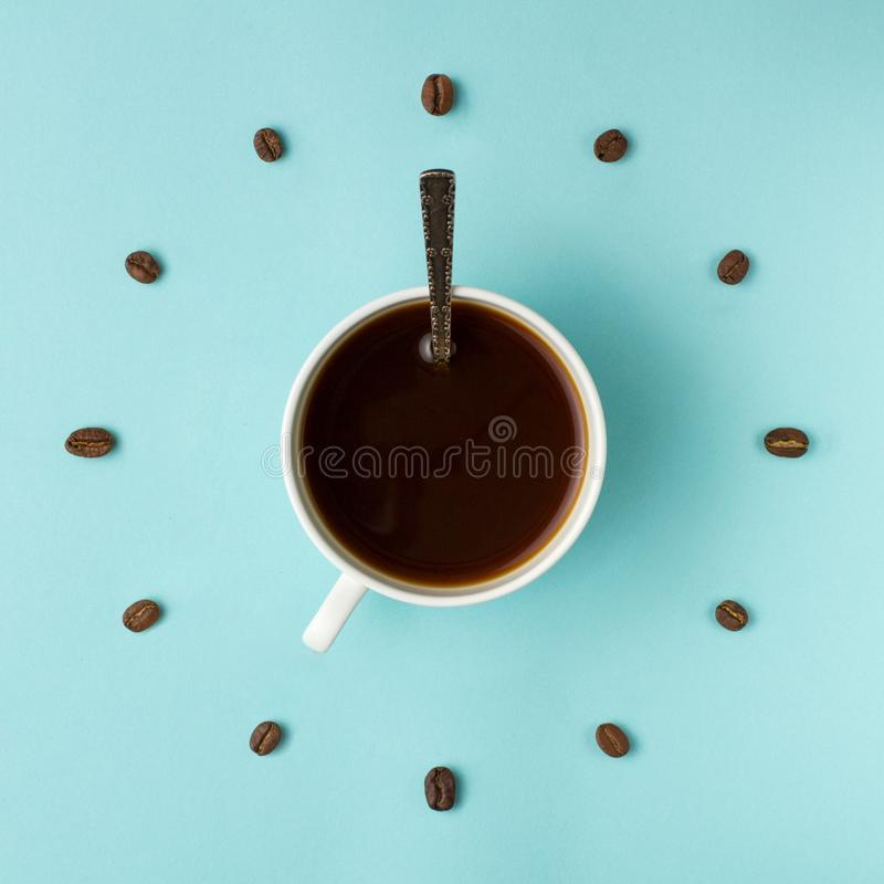 Coffee cup and roasted beans arranged as clock face on blue background, top view. Coffee time symbol. Interesting idea energy and. Refreshment concept royalty free stock image
