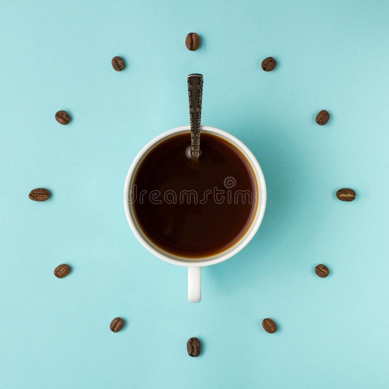 Coffee cup and roasted beans arranged as clock face on blue background, top view. Coffee time symbol. Interesting idea energy and royalty free stock photos