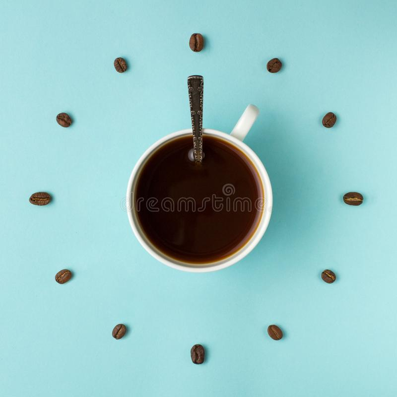 Coffee cup and roasted beans arranged as clock face on blue background, top view. Coffee time symbol. Interesting idea energy and. Refreshment concept stock photography